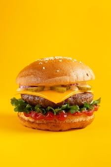노란색 배경에 햄버거입니다. 패스트 푸드, 정크 푸드 개념