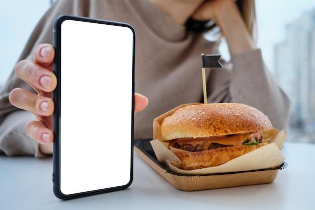 Гамбургер на столе и девушка держит смартфон с копией пространства.