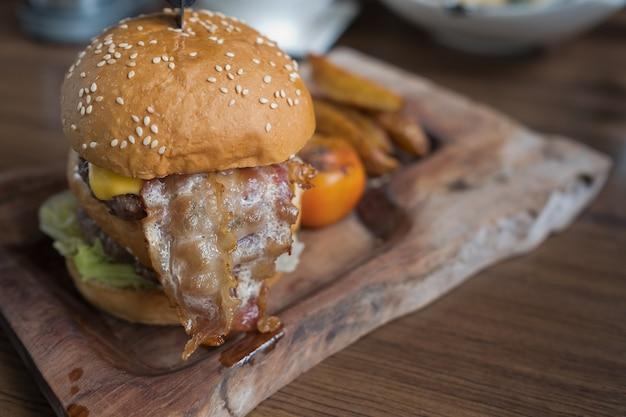 Гамбургер на деревянном фоне, нездоровая еда
