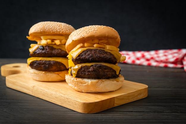 チーズとフライドポテトを添えたハンバーガーまたはビーフバーガー-不健康なフードスタイル