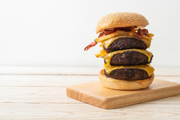 チーズ、ベーコン、フライドポテトを添えたハンバーガーまたはビーフバーガー-不健康なフードスタイル