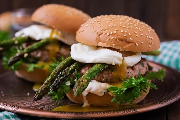 Гамбургер (сэндвич) с куриным бургером, листьями салата, спаржей, яйцом пашот и соусом тар-тар