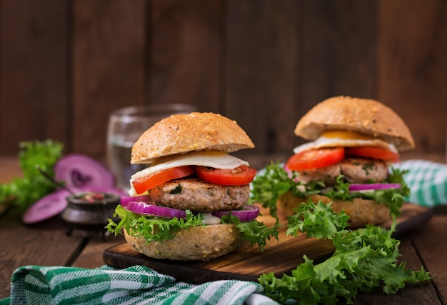 Гамбургер (сэндвич) с куриным гамбургером, салатом, томатом, жареным яйцом и соусом тартар