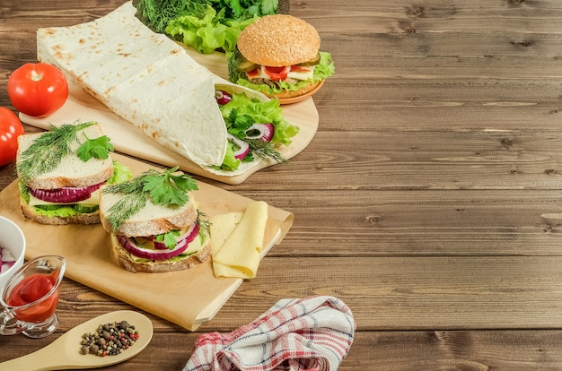 Hamburger, shawarma, sandwiches on a dark wooden background with copy space.