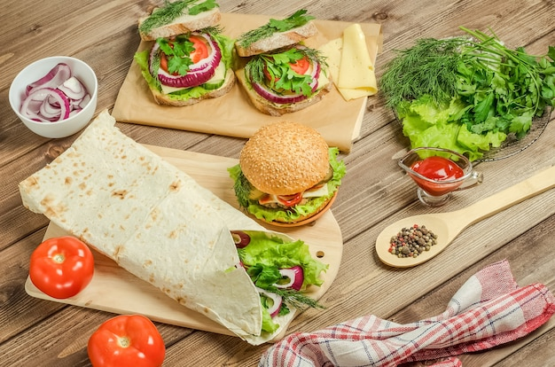 Hamburger, shawarma, sandwiches on a dark wooden background.
