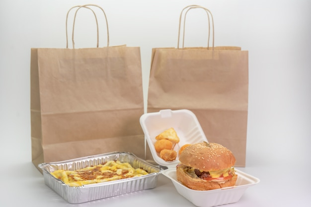 Hamburger in a takeaway container and paper bag on white background