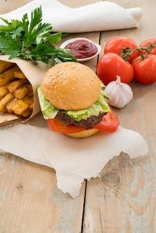 Гамбургер вкусный картофель фри и помидоры