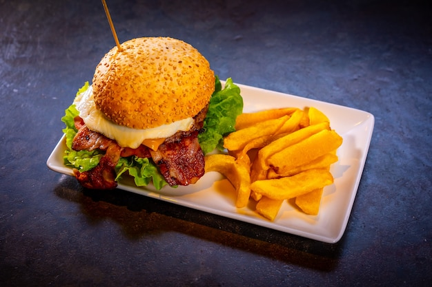 白いプレートに、黒い背景にベーコンとフライドポテトとハンバーガー