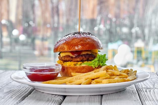 Гамбургер с говяжьей котлетой, сыром, картофелем фри, томатным салатом, соусом и кетчупом на тарелке