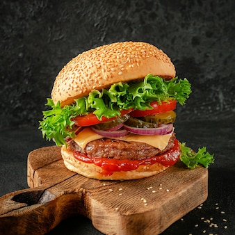Hamburger with cheddar cheese on wooden board