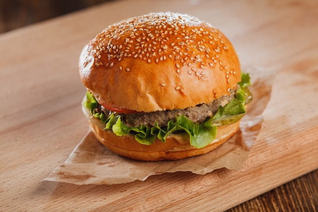 Hamburger with cheese on wooden table