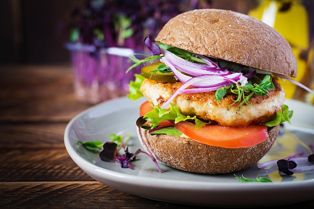 Hamburger with chicken burger, tomatoes, pickled cucumber and red onion