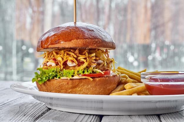 Гамбургер с куриной котлетой, сыром, картофелем фри, томатным салатом, соусом и кетчупом на тарелке