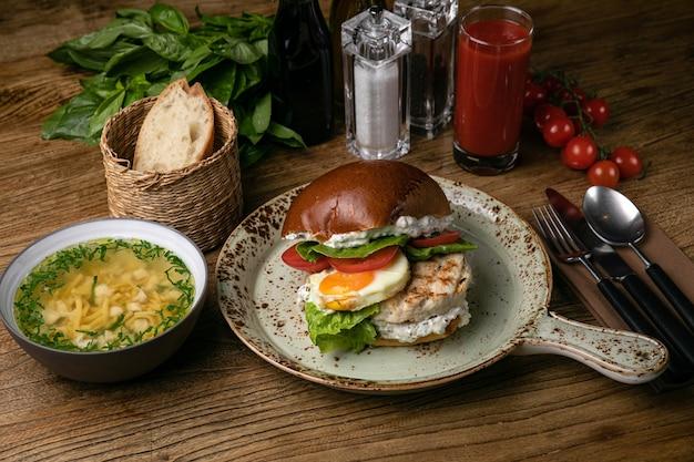 テーブルの上にチキンカツレツスープトマトジュースバジルトマトとハンバーガー