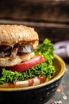 鶏肉、漬物、揚げ玉ねぎのハンバーガー。木製の背景にビーフバーガー。垂直方向の画像。テキストの場所