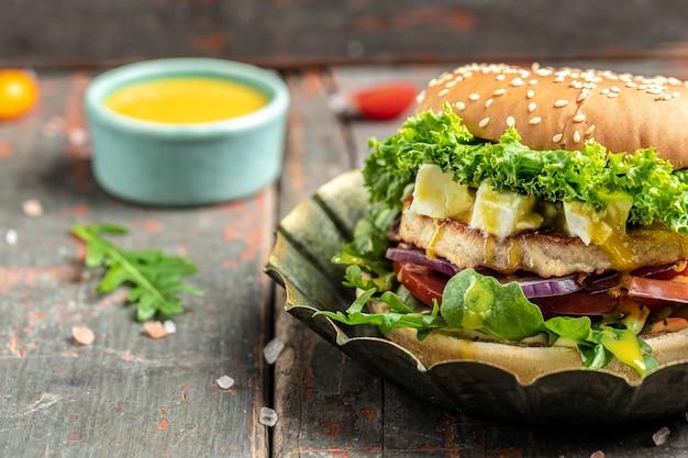 木製のテーブルにフェタチーズとチキンビーフを添えたハンバーガー。不健康な栄養をもたらすダイエット誘惑の象徴。テキストの場所。