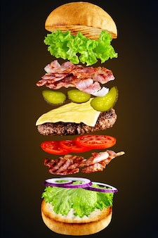 Гамбургер с летающими ингредиенты, изолированных на темноте. высокое разрешение изображения. летающие ингредиенты для домашнего бургера на темноте. отличный вкусный домашний бургер с летающими ингредиентами