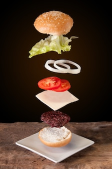 Hamburger with flying ingredients placed on wooden planks