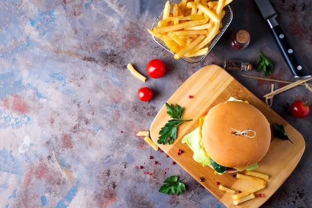 ハンバーガー、フライドポテト、ビール、石テーブル