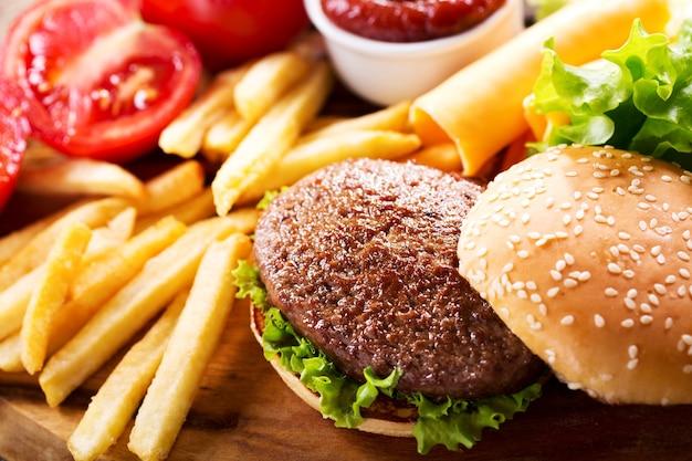 Гамбургер с картофелем фри на деревянной доске