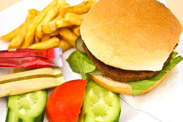Hamburger with french fries, sliced cucumbers and tomatoes