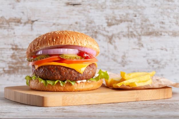 フライド ポテト、トマト、チーズ、タマネギ、レタス、きゅうりを木の板に載せたハンバーガー
