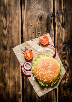 A hamburger with fresh tomatoes, onions and spices. on wooden table.  top view.
