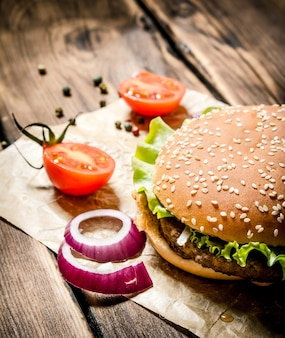 A hamburger with fresh tomatoes, onions and spices. on wooden table.
