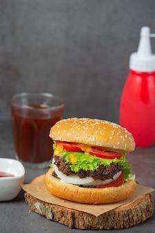 Гамбургер с жареным мясом, помидорами, солеными огурцами, листьями салата и сыром.