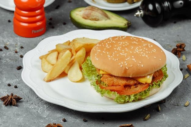 皿にフライドポテトとサラダを添えたハンバーガー