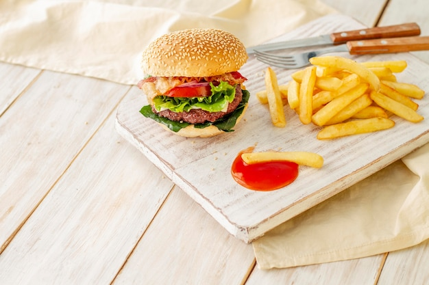 Hamburger with fries and sauce on wooden board