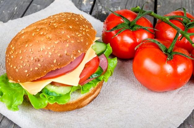 Гамбургер с ветчиной, сыром, огурцами, помидорами и салатом на льняной салфетке рядом с веткой красного сочного помидора
