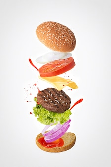 Hamburger with ingredients fliying