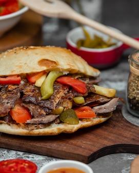 Гамбургер с шашлыком, помидорами и огурцами