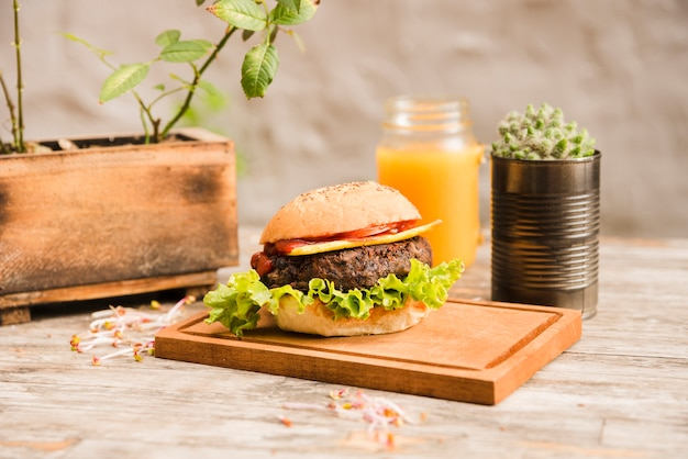 Hamburger with lettuce and cheese on chopping wooden board with juice bottle on table