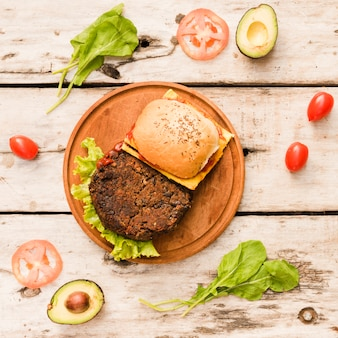 Hamburger with lettuce and cheese on circular wooden board on table