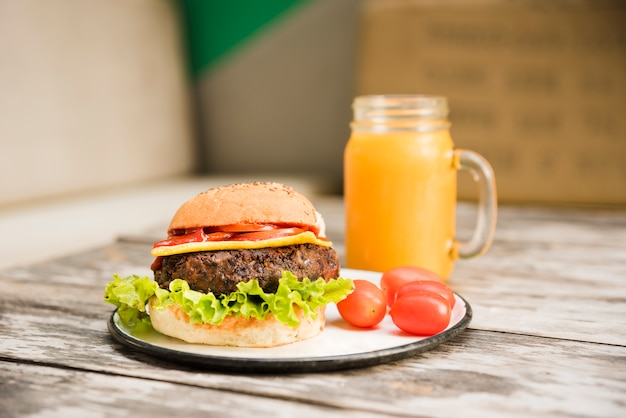 Hamburger with lettuce; tomatoes and cheese on plate with juice jar over the table