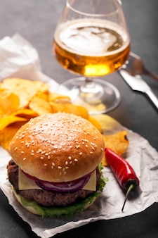 Hamburger with meat cutlet. potato chips and beer