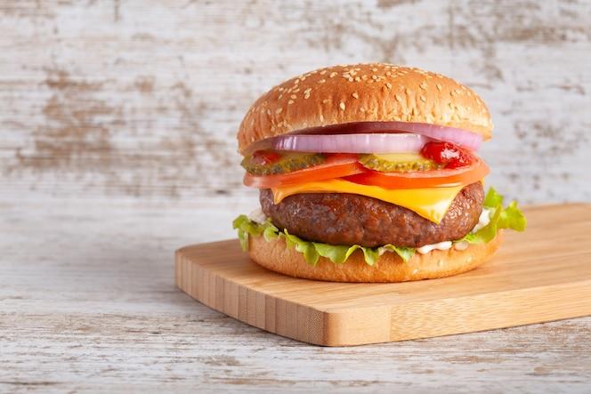 木の板にトマト、チーズ、玉ねぎ、レタス、きゅうりのハンバーガー