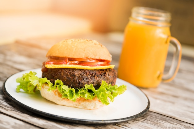Hamburger with tomatoes; cheese and lettuce served with juice glass on wooden table