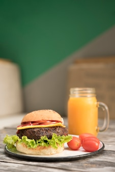 Hamburger with tomatoes and juice jar on table