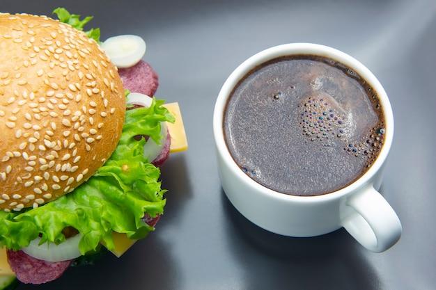 회색에 야채와 소시지와 커피와 햄버거.