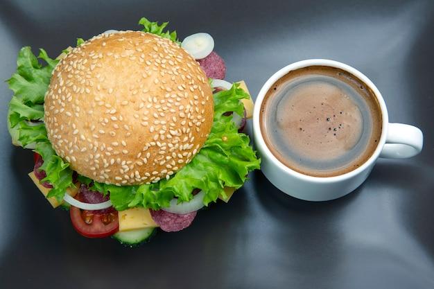 Гамбургер с овощами и колбасой и кофе на сером.
