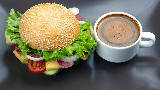 Hamburger with vegetables and sausage and coffee on a gray surface. fast food and breakfast. calories and diet.