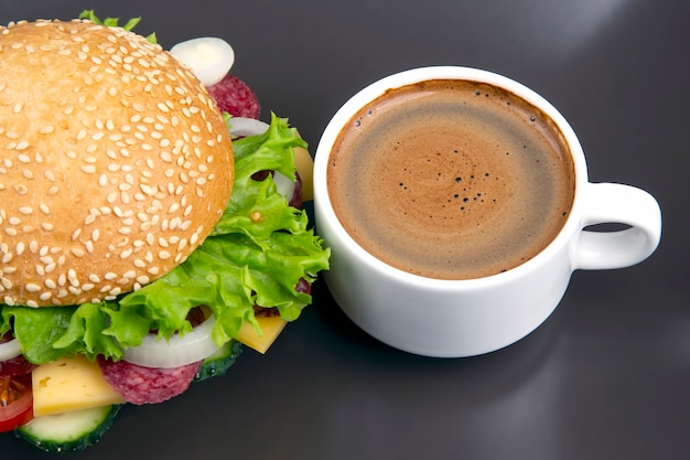 Hamburger with vegetables and sausage and coffee on a gray table. fast food and breakfast. calories and diet.