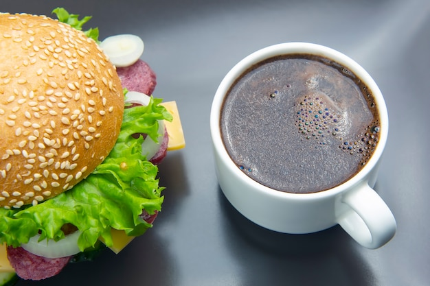 Hamburger with vegetables and sausage and coffee on a gray.