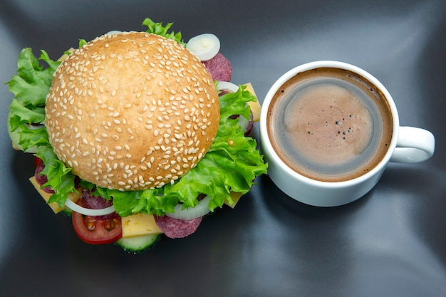 Hamburger with vegetables and sausage and coffee on a gray