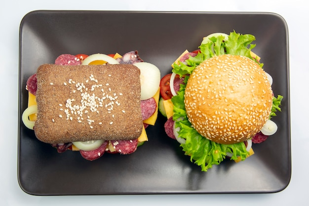 Hamburger with vegetables and sausage on a gray table. fast food and breakfast. calories and diet.
