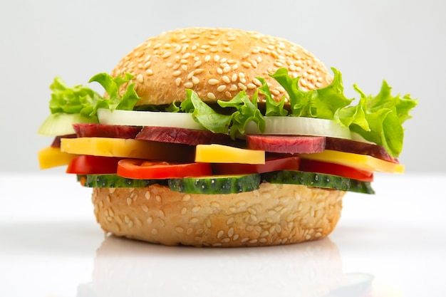 Hamburger with vegetables and sausage on a white