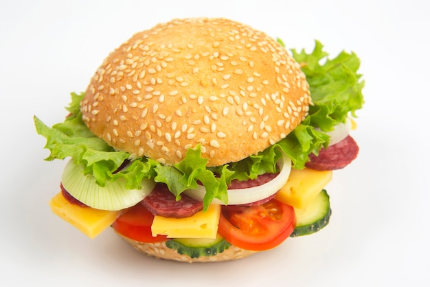 Hamburger with vegetables and sausage on white